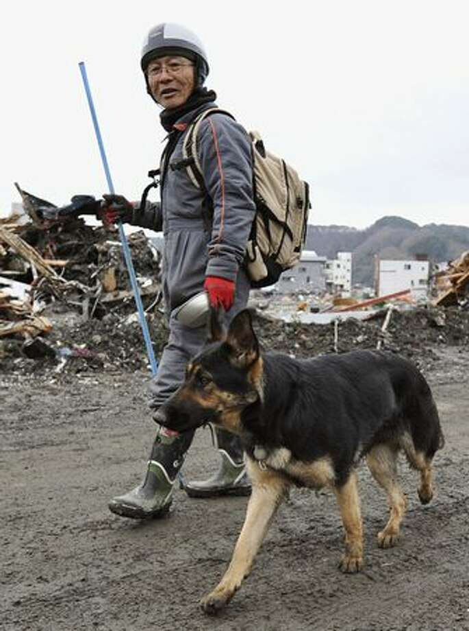 Ko Nakamura, a victim of the March 11 earthquake and tsunami, walks around his devastated home area searching for missing people with his dog in Otsuchi, northern Japan, Monday, March 21, 2011. (AP Photo/Kyodo News) Photo: Associated Press / Associated Press