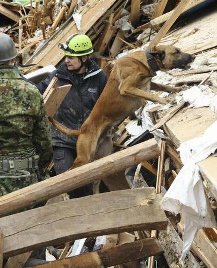 Volunteers from the Netherlands and their search dog look for missing people in an devastated area in Ofunato, northern Japan, Tuesday, March 22, 2011, following the March 11 earthquake and tsunami. (AP Photo/The Yomiuri Shimbun, Shohei Izumi) Photo: Associated Press / Associated Press