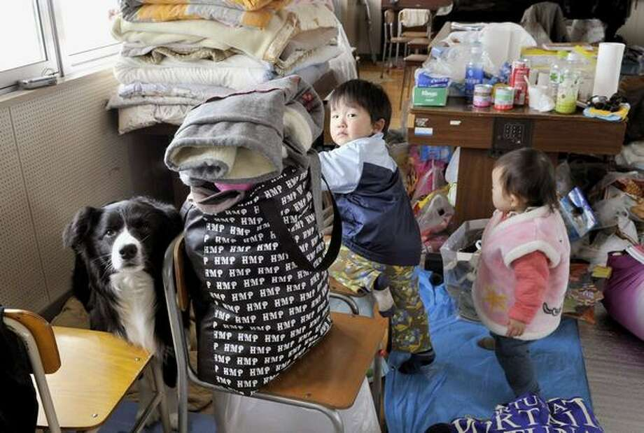 Evacuated children and dog rest at a shelter in Ishinomaki, northern Japan Tuesday, March 22, 2011. (AP Photo/Kyodo News) Photo: Associated Press / Associated Press