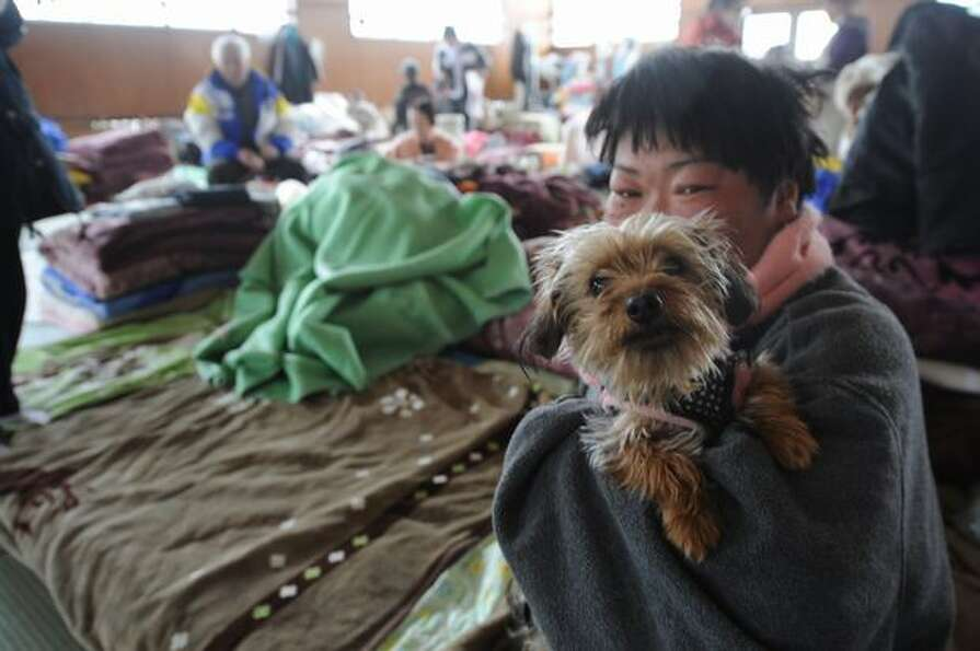 A women sits with her dog at an evacuation center in the port town of Higashimatsushima, Japan, on M
