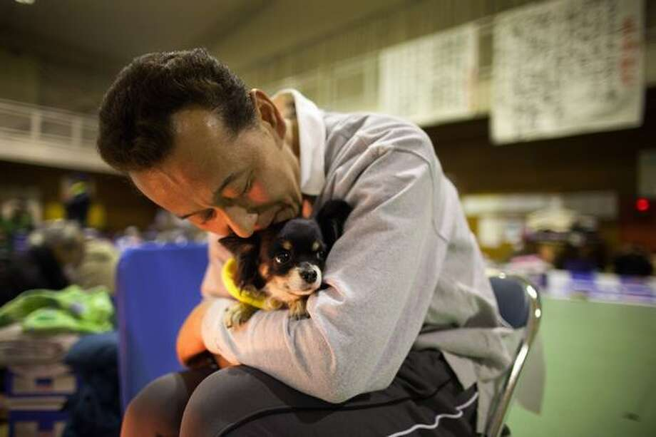A man hugs his dog to keep it warm as earthquake victims pack an evacuation center March 20, 2011 in Ofunato, Japan. Photo: Getty Images / Getty Images
