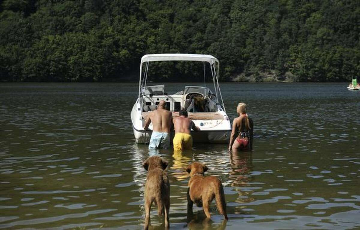 Dogs watch their owners push a boat on Aug. 22, 2010, along Lake Slapy, about 50 kilometers from Prague, Czech Republic.
