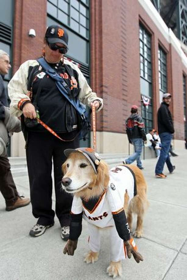 A fan of the San Francisco Giants and her dog pose outside of AT&T Park prior to Game One of the 2010 Major League Baseball World Series on October 27, 2010 in San Francisco, California. Photo: Getty Images / Getty Images