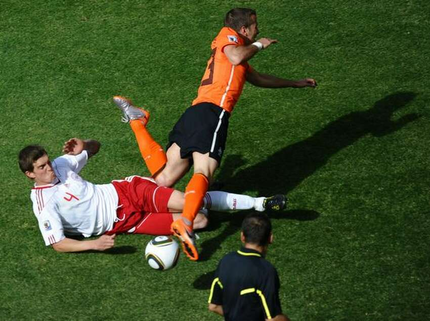 Denmark's defender Daniel Agger (L) tackles Netherlands' midfielder Rafael van der Vaart (C) in front of French referee Stephane Lannoy during the Group E first round 2010 World Cup football match Netherlands vs. Denmark on June 14, 2010 at Soccer City stadium in Soweto, suburban Johannesburg.