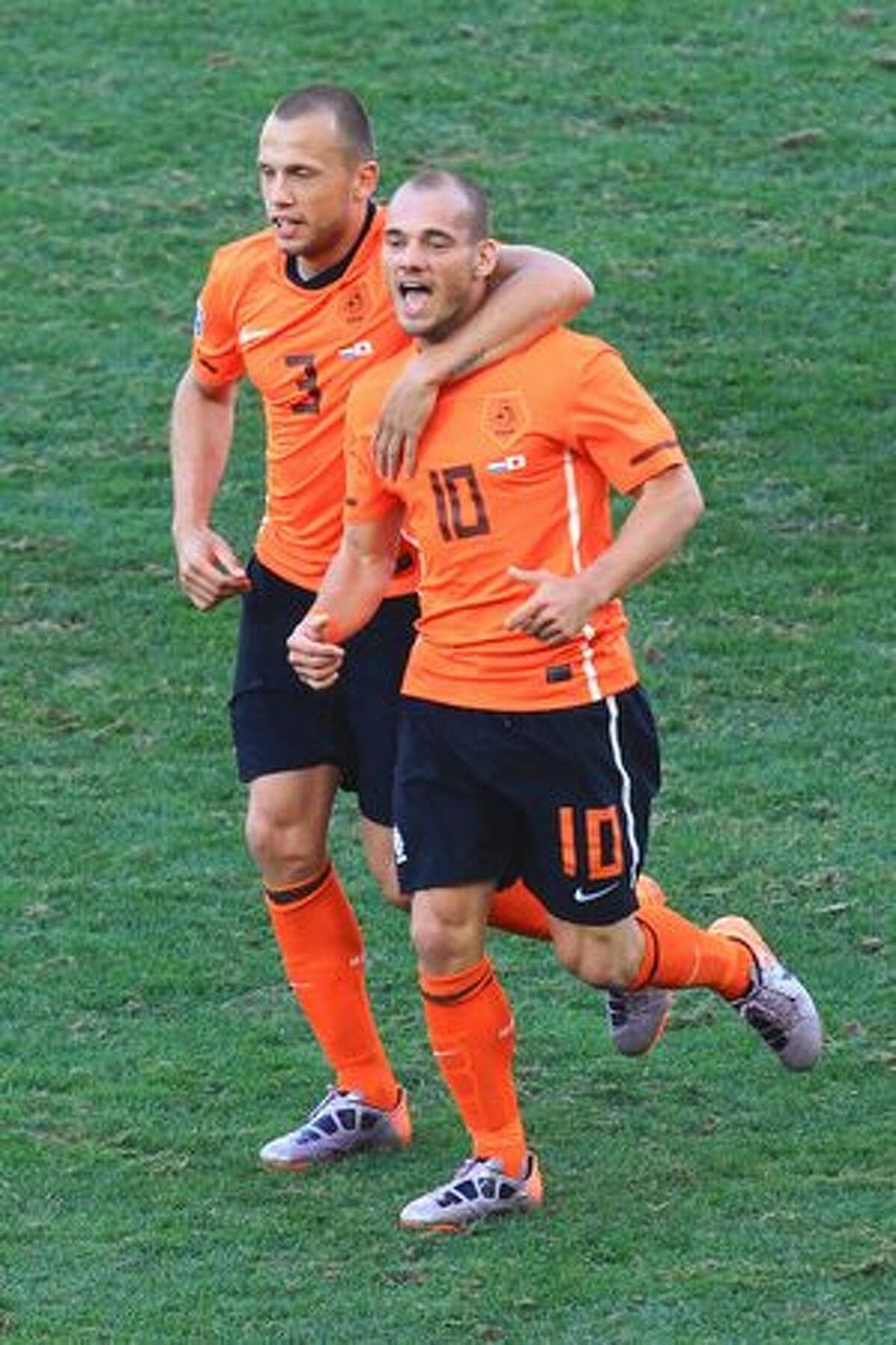 Wesley Sneijder of the Netherlands (R) celebrates scoring the opening goal with team mate John Heitinga during the 2010 FIFA World Cup South Africa Group E match between Netherlands and Japan at Durban Stadium on June 19, 2010 in Durban, South Africa.