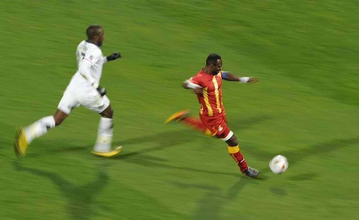 Ghana's defender John Mensah (R) escapes a US player during the 2010 World Cup round of 16 football match USA vs. Ghana on June 26, 2010 at Royal Bafokeng stadium in Rustenburg.
