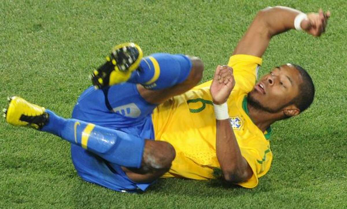 Brazil's defender Michel Bastos falls on the pitch during the 2010 World Cup round of 16 football match Brazil vs. Chile at Ellis Park stadium in Johannesburg. Brazil won 3-0.