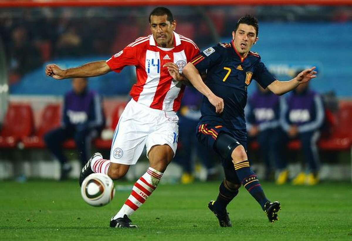 Paulo Da Silva of Paraguay and David Villa of Spain tussle for the ball during the 2010 FIFA World Cup South Africa Quarter Final match between Paraguay and Spain at Ellis Park Stadium on July 3, 2010 in Johannesburg, South Africa.