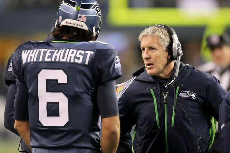 Head coach Pete Carroll of the Seattle Seahawks talks with quarterback Charlie Whitehurst #6 during