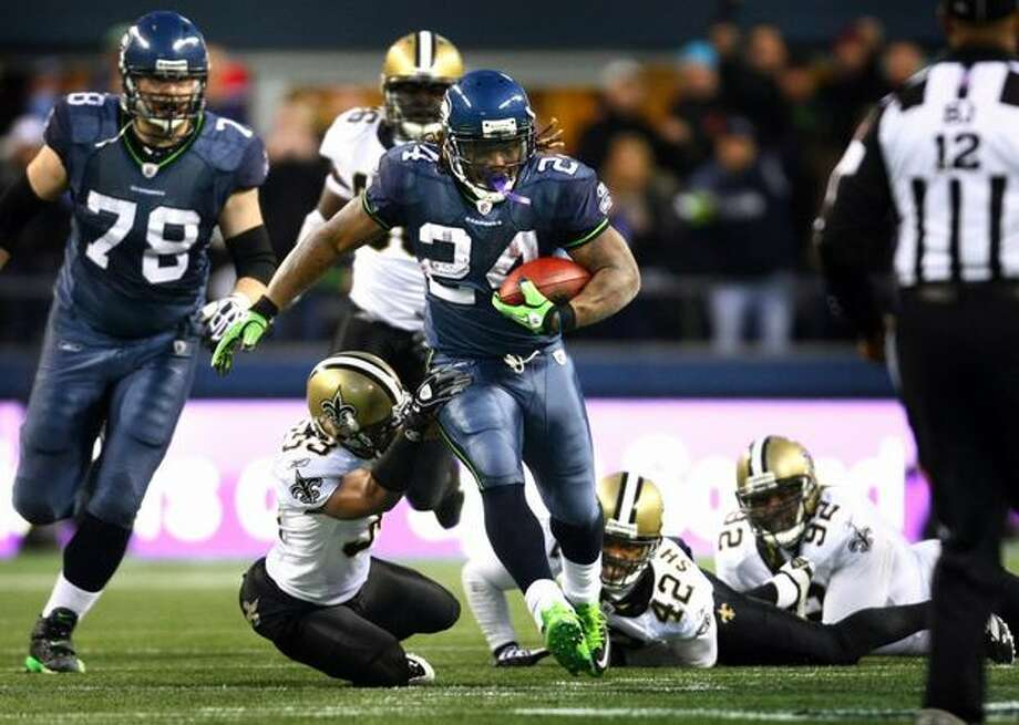 Seattle Seahawks running back Marshawn Lynch breaks through New Orleans defenders during an epic 67 yard touchdown run in the fourth quarter against the defending Super Bowl champs. Photo: Joshua Trujillo, Seattlepi.com / seattlepi.com