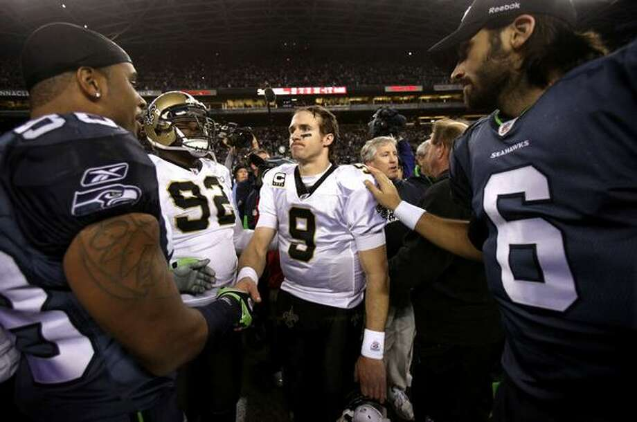 New Orleans quarterback Drew Brees is greeted by Seahawks players Raheem Brock, left, and Charlie Whitehurst after the Seahawks defeated the Saints 41-36. Photo: Joshua Trujillo, Seattlepi.com / seattlepi.com