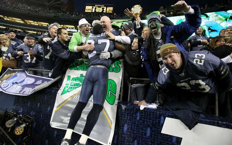Seattle's Jordan Babineaux jumps into the arms of fans after the Hawks defeated the New Orleans Saints 41-36. Photo: Joshua Trujillo, Seattlepi.com / seattlepi.com