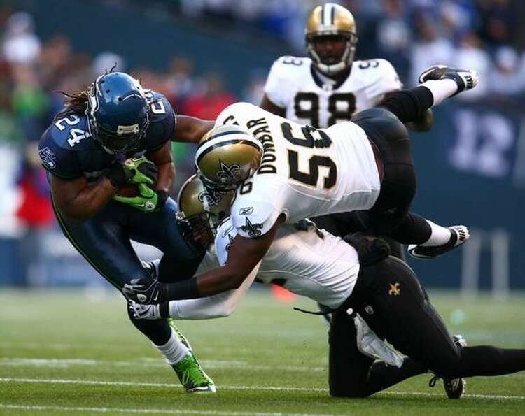 Seattle's Marshawn Lunch is stopped by New Orleans players Jo-Lonn Dunbar (56) and Darren Sharper (4