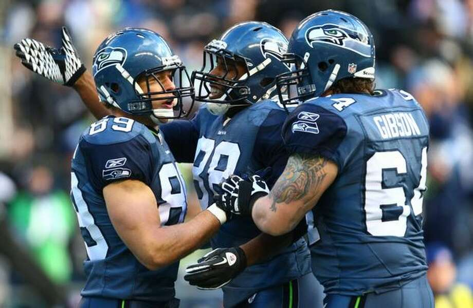 Seahawks Cameron Morrah (88) and Mike Gibson (64) celebrate with John Carlson, left, after Carlson's first-quarter touchdown on a pass from quarterback Matt Hasselbeck. Photo: Joshua Trujillo, Seattlepi.com / seattlepi.com