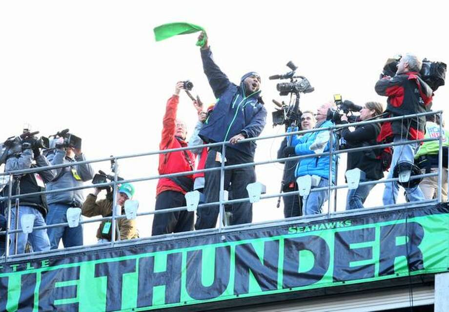 Former Seahawk Walter Jones raises the 12th Man flag before the game. Photo: Joshua Trujillo, Seattlepi.com / seattlepi.com