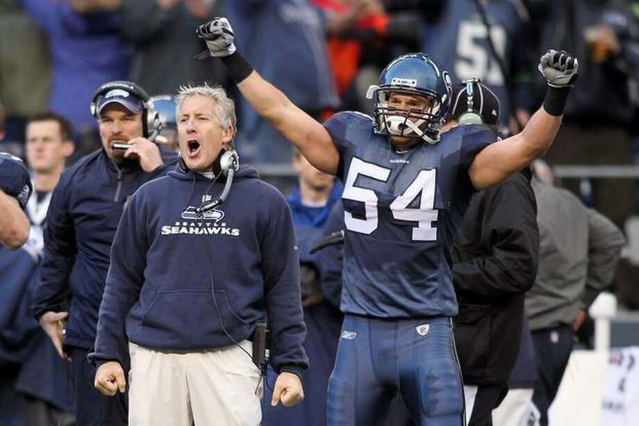 Head coach Pete Carroll and Will Herring #54 of the Seattle Seahawks celebrate a fourth-down stop by the Seahawks in the third quarter against the New Orleans Saints during the 2011 NFC wild-card playoff game at Qwest Field on January 8, 2011 in Seattle, Washington. Photo: Getty Images / Getty Images