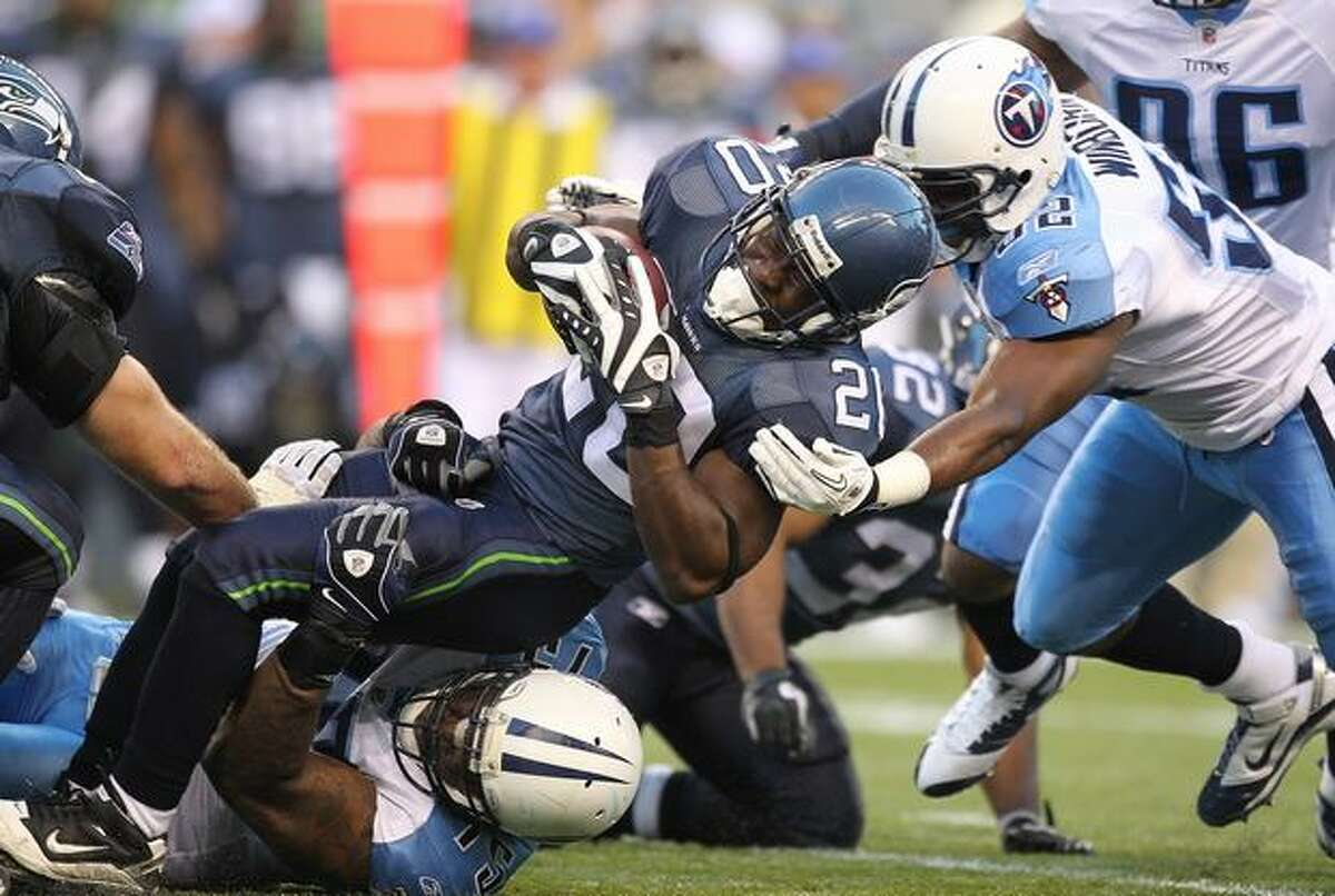 Running back Justin Forsett #20 of the Seahawks rushes during the preseason game against Jovan Haye #75 and Jamie Winborn #52 of the Tennessee Titans at Qwest Field on August 14, 2010 in Seattle, Washington. The Seahawks defeated the Titans 20-18.