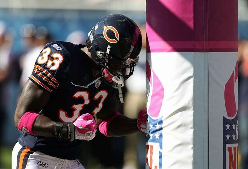 Charles Tillman #33 of the Chicago Bears uses the goal post as a punching bag during warm-ups before a game against the Seattle Seahawks.