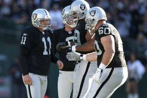 Sebastian Janikowski #11 of the Oakland Raiders is congratulated by teammates after he kicked a field goal against the Seattle Seahawks.