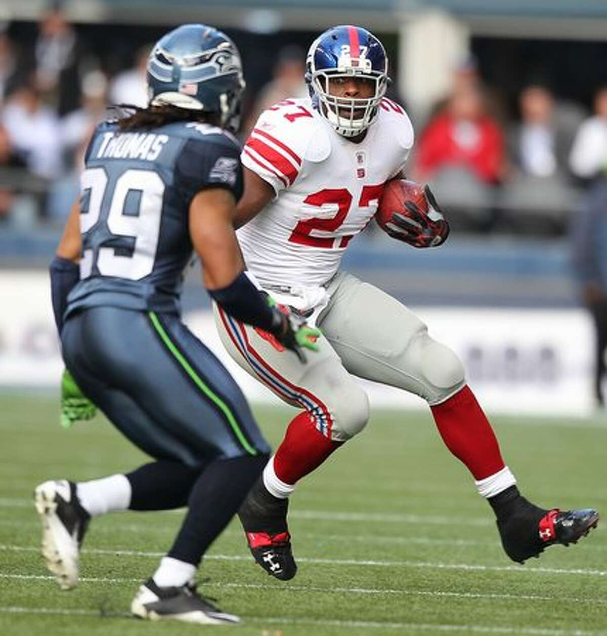 Running back Brandon Jacobs #27 of the New York Giants rushes against Earl Thomas #29 of the Seattle Seahawks.
