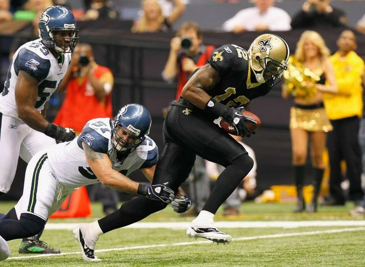 Marques Colston (12) of the New Orleans Saints scores a touchdown as he breaks a tackle by Lofa Tatupu (51) of the Seattle Seahawks at Louisiana Superdome in New Orleans.