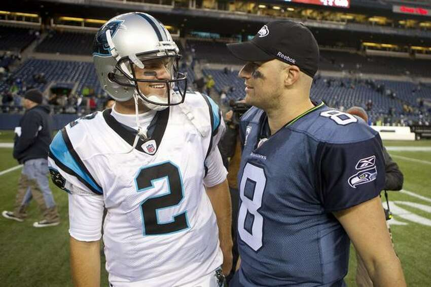 Carolina quarterback Jimmy Clausen (left) and the Seahawk's Matt Hasselbeck meet up after the game that was won by the Seahawks.