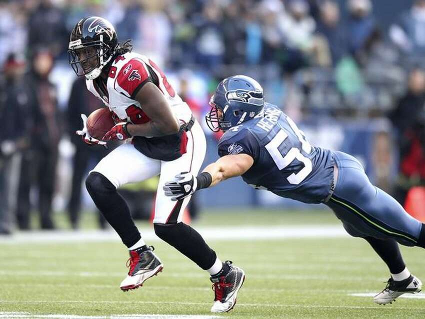 Wide receiver Roddy White #84 of the Atlanta Falcons rushes against Will Herring #54 of the Seattle Seahawks.
