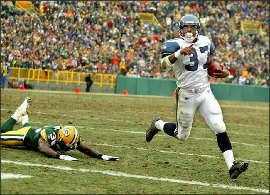 Seattle running back Shaun Alexander glides into the end zone past flailing Packers defender Nick Collins as he went around the left side in the second quarter for his 28th touchdown of the season to break the record he shared with Priest Holmes. Photo: Scott Eklund, Seattle Post-Intelligencer / Seattle Post-Intelligencer