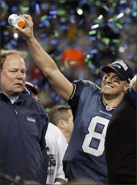 Matt Hasselbeck pretends to pour Gatorade on coach Mike Holmgren's head during the trophy presentati