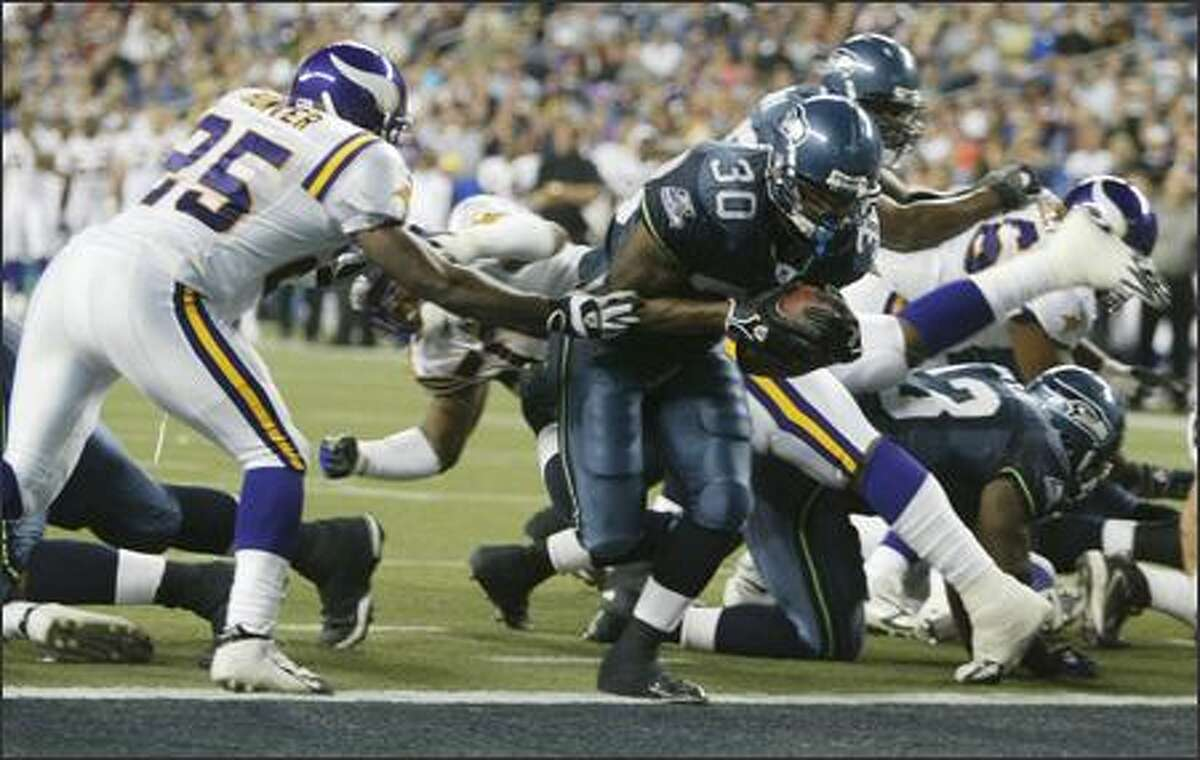 Seattle Seahawks' Marquis Weeks breaks away from Minnesota Vikings Will Hunter to score during fourth quarter action.