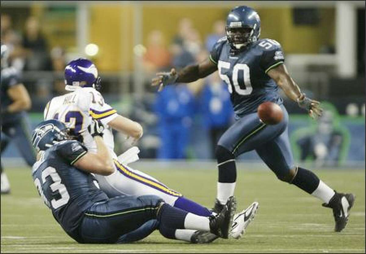 Seattle Seahawks' Craig Terrill tackles Minnesota Vikings Shaun Hill as he intentionally grounds the ball during fourth quarter action. The ball bounced off of Seahawks' Cleveland Pinkney (50).