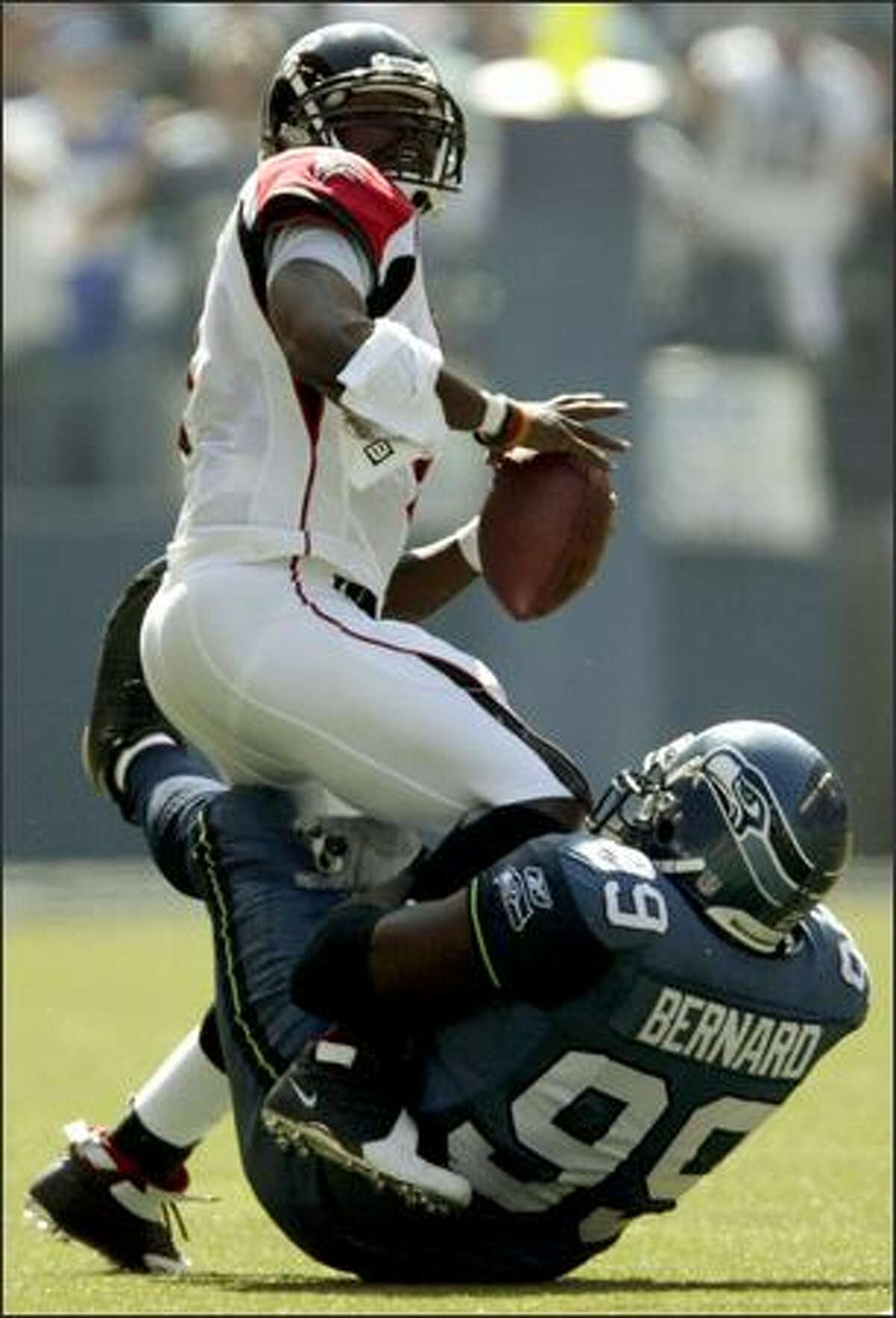 Michael Vick is hog-tied by Seahawks defensive lineman Rocky Bernard in the first quarter. Vick was sacked three times.