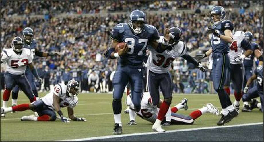 Shaun Alexander, with Texans cornerback Demarcus Faggins (38) in hot pursuit, crosses the goal line for his first of two touchdowns, a four-yard run, in the first quarter. Photo: Dan DeLong, Seattle Post-Intelligencer / Seattle Post-Intelligencer