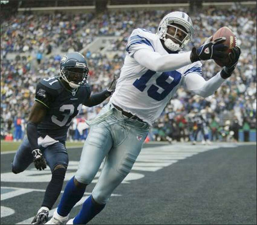 Dallas Cowboys Keyshawn Johnson pulls in a 5-yard touchdown pass as Seattle Seahawks cornerback Kelly Herndon defends during 1st quarter play.