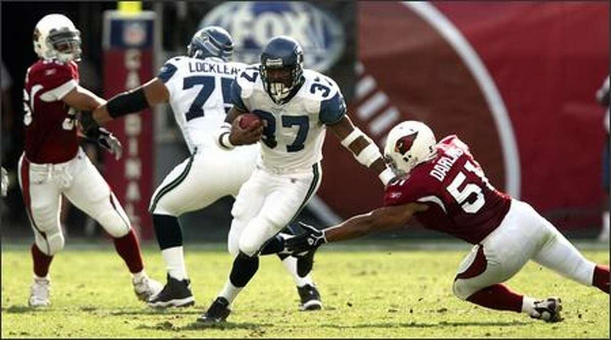 Seahawks running back Shaun Alexander runs for six yards against Arizona Cardinals linebacker James Darling during the first quarter.