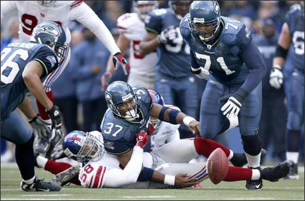 After getting hit by New York Giants linebacker Antonio Pierce, Seahawks running back Shaun Alexander watches his fumble bounce away as Jerramy Stevens (left) and Walter Jones (71) pursue during the second quarter. Stevens recovered the ball.