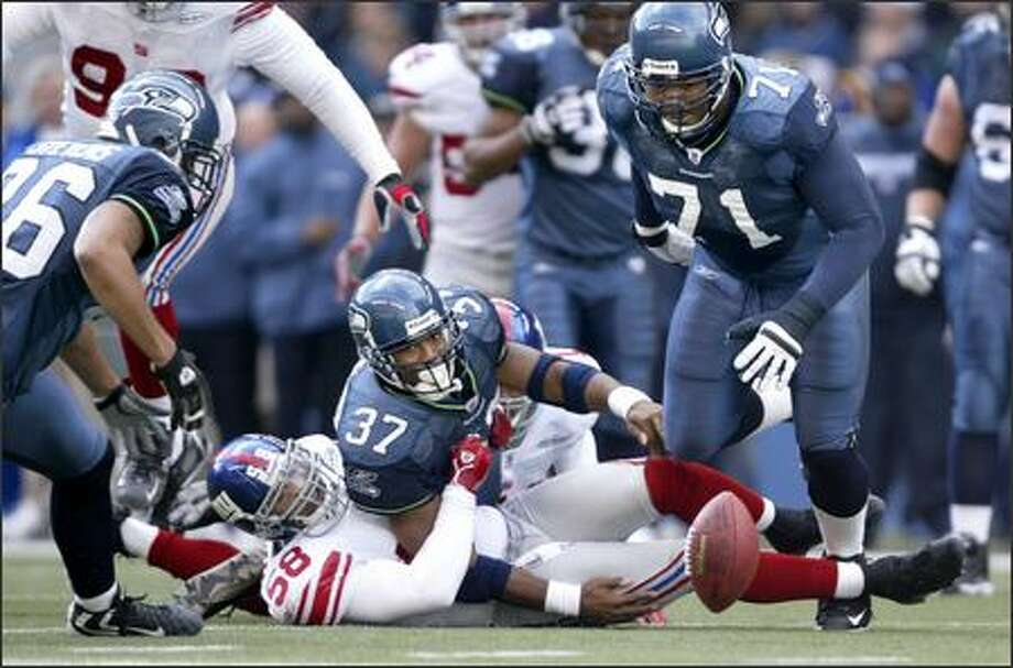 After getting hit by New York Giants linebacker Antonio Pierce, Seahawks running back Shaun Alexander watches his fumble bounce away as Jerramy Stevens (left) and Walter Jones (71) pursue during the second quarter. Stevens recovered the ball. Photo: Dan DeLong, Seattle Post-Intelligencer / Seattle Post-Intelligencer