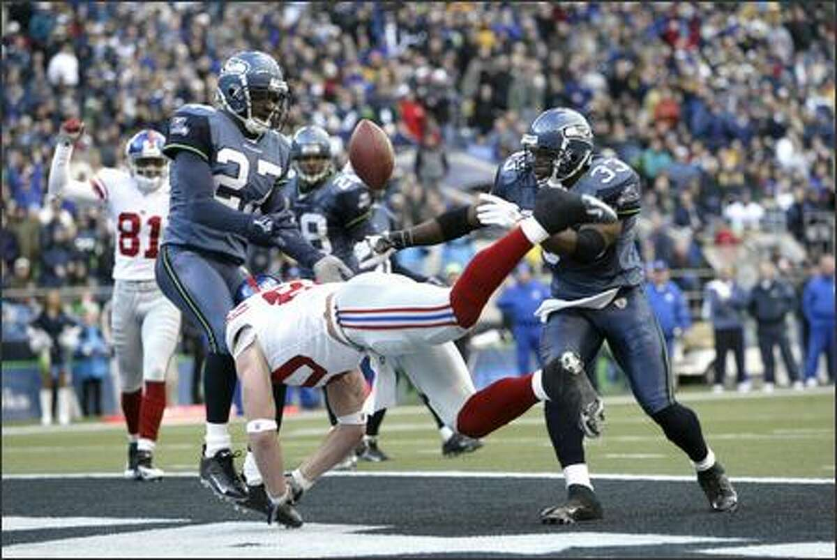 Seattle Seahawks safety Marquand Manuel (33) hits New York Giants tight end Jeremy Shockey, causing him to fumble in the second quarter. On left is Seahawks cornerback Jordan Babineaux (27).