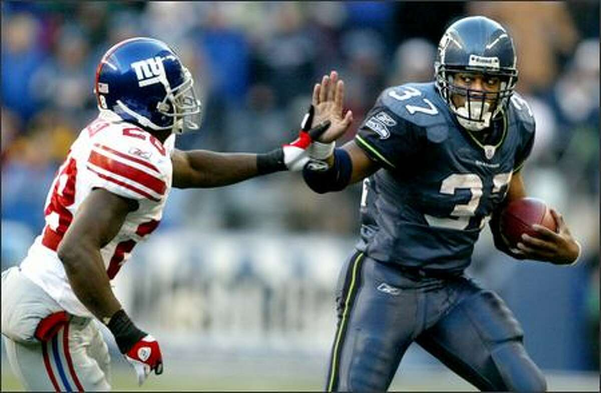 Seahawk's running back Shaun Alexander fights off Giants defender Gibril Wilson during a second-half run. The Seahawks went on to beat the Giants 24-21 in overtime.