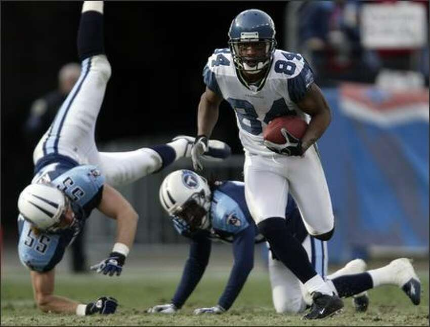 Bobby Engram takes off for 56 yards on a third-quarter catch and run, leaving Titans Brad Kassell and Reynaldo Hill on the ground. It was the Seahawks' longest pass play of the season.