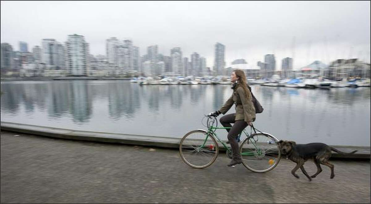A woman walks her dog behind her bike along the False Creek waterfront in Vancouver, British Columbia.