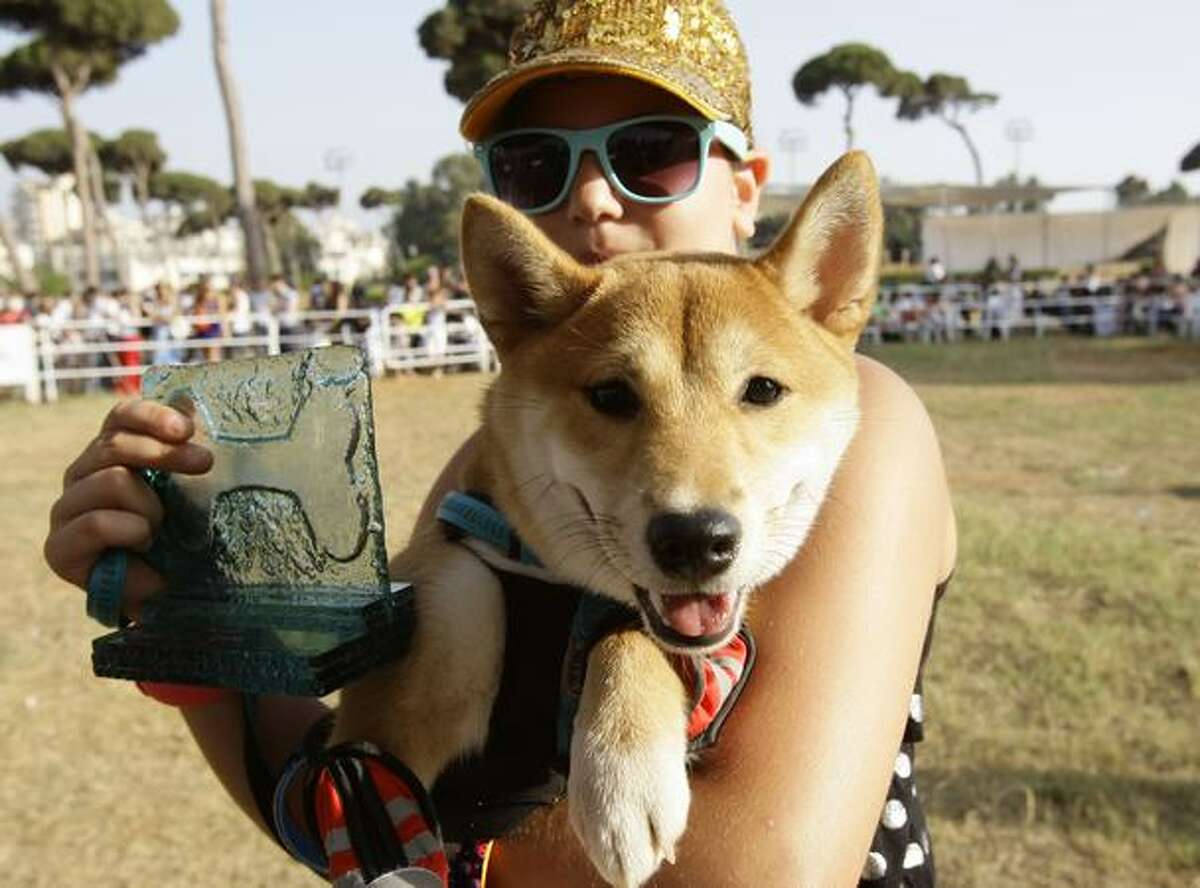 A Lebanese woman shows off her award and her pet during the BETA Animal Show in Beirut, a contest to name