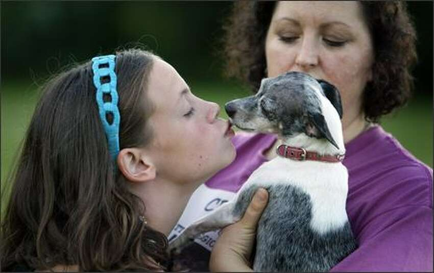 Bella Stribling, 13, gets a kiss from Cricket, held by her Aunt Celeste Virago Lowe after demonstrating how fast the little dog can go.