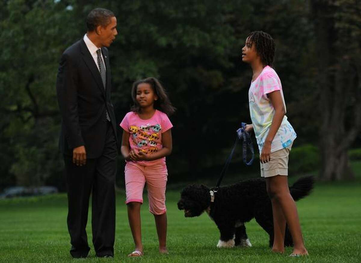 President Barack Obama (L) is greeted by his daughters Sasha (2nd L) and Malia and their dog Bo upon his return to the White House in Washington following a trip to Ohio and Pennsylvania.