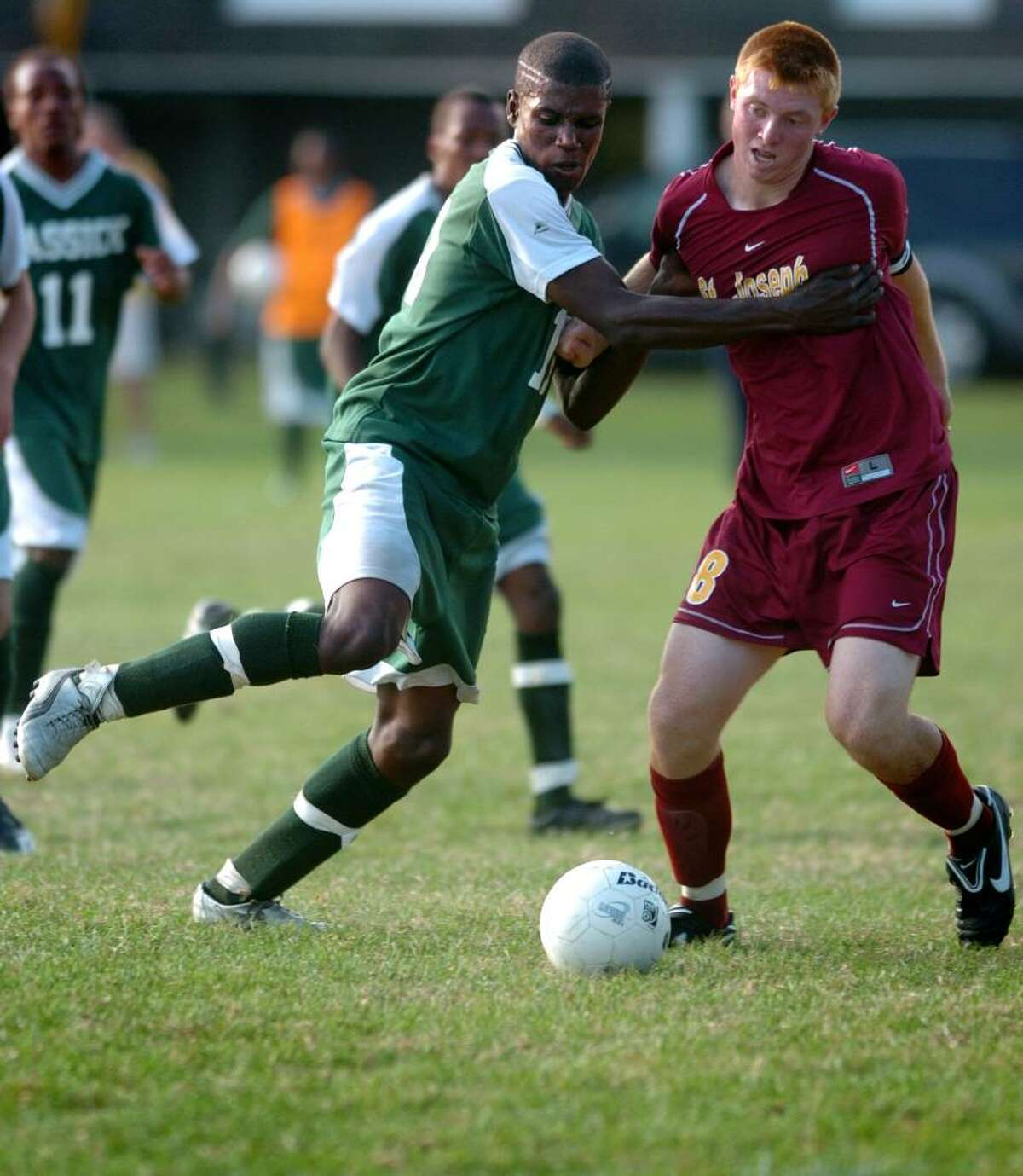 Bassick's Romaro Johnson holds back St. Joseph's Brendan Nugent as he goes to kick the ball during the first half of Wednesday's game at Seaside Park in Bridgeport, Conn.