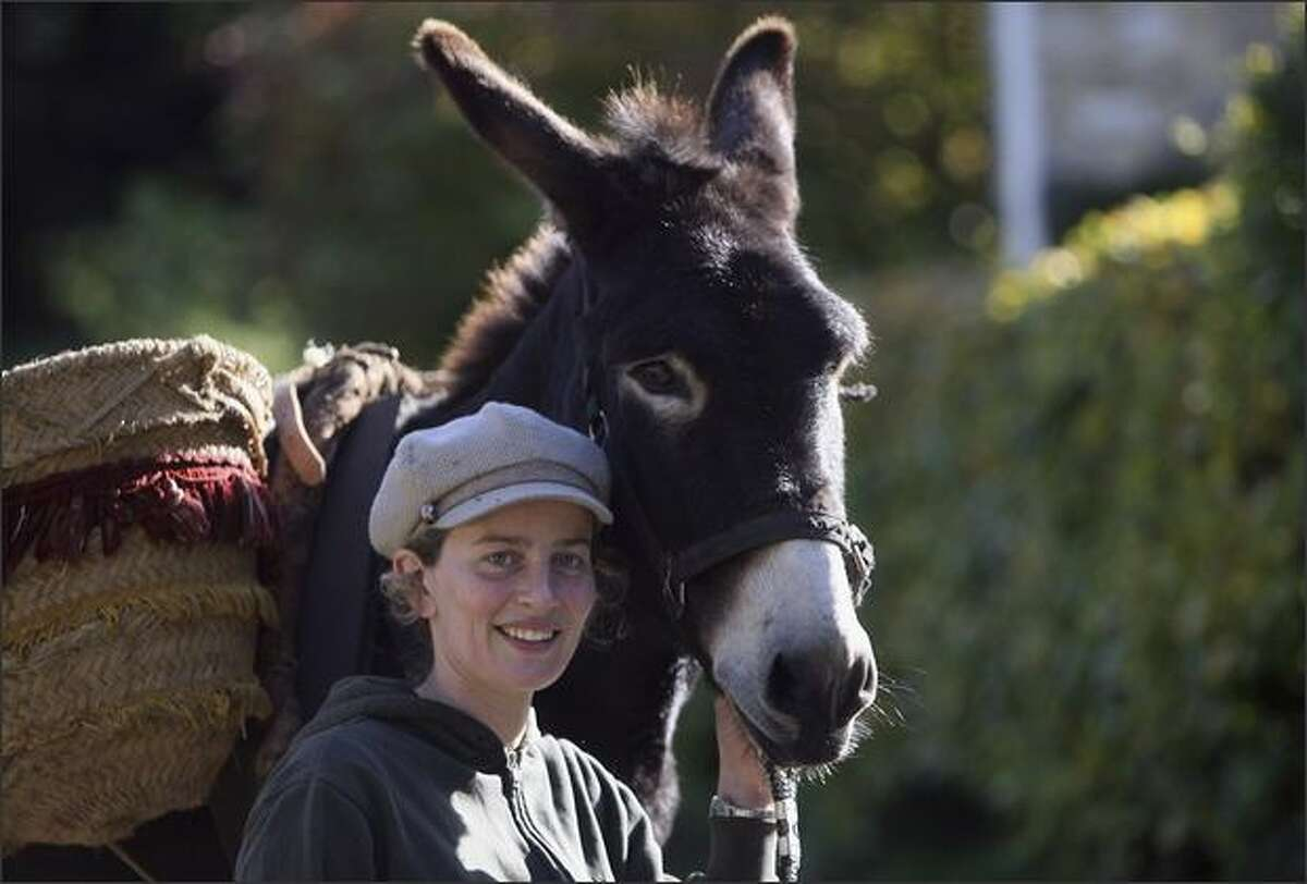 Chalford resident Anna Usborne with the town's donkey Teddy, as they prepare to go and deliver groceries in Chalford, England. Parts of Chalford, near Stroud in Gloucestershire, are so steep, residents cannot drive their cars up the narrow paths to the doors of their homes and have employed a donkey to help carry heavy bags 100 metres up the steep slopes. Historically, because of the difficulty in accessing the houses, donkeys were used in the Cotswold village as late as the 1930s to make deliveries, carrying bread, coal and many other household items to people's doorsteps.