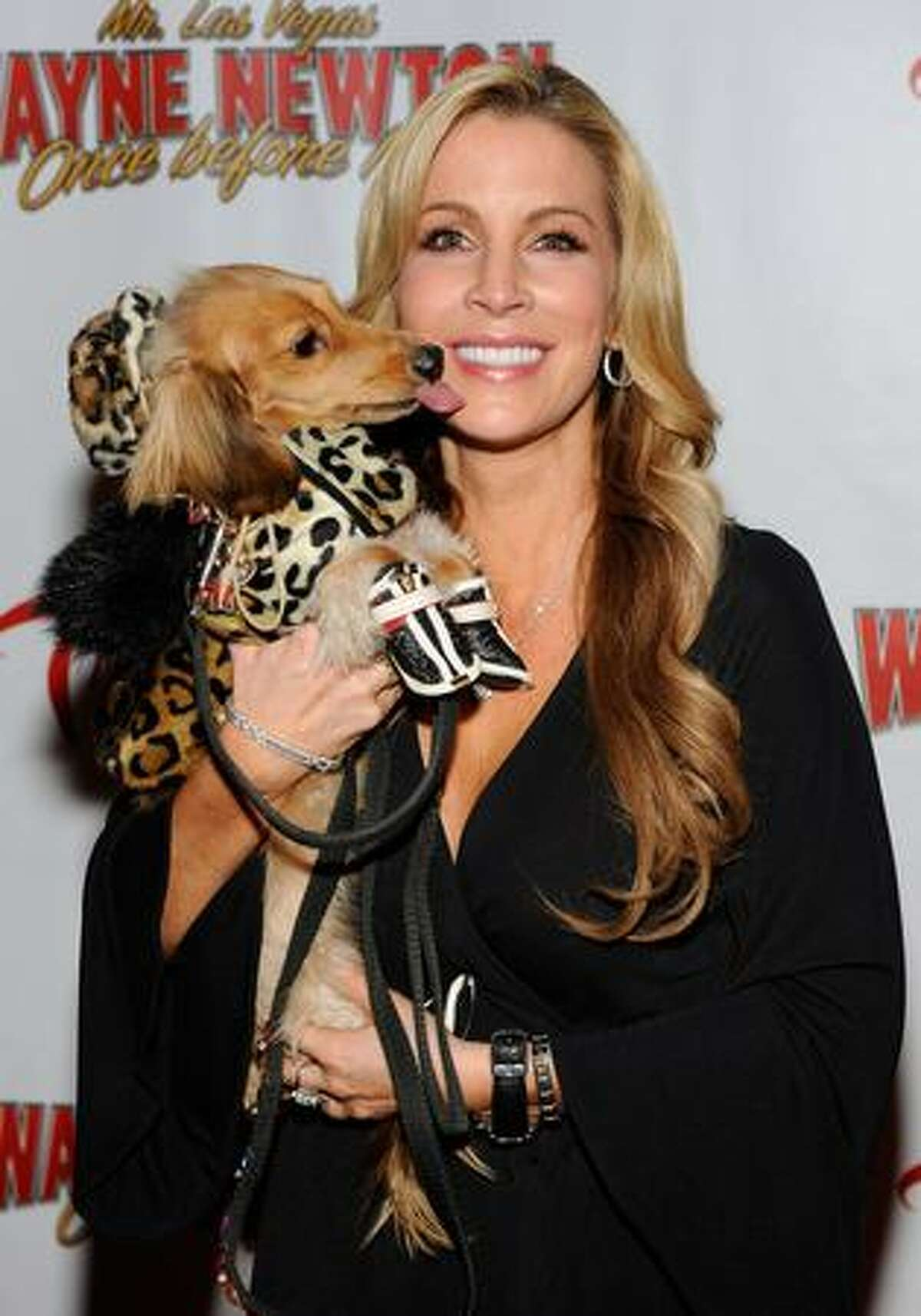 Television entertainment reporter Alicia Jacobs holds her dog Sparkle as she arrives at the opening of Wayne Newton's limited-engagement production