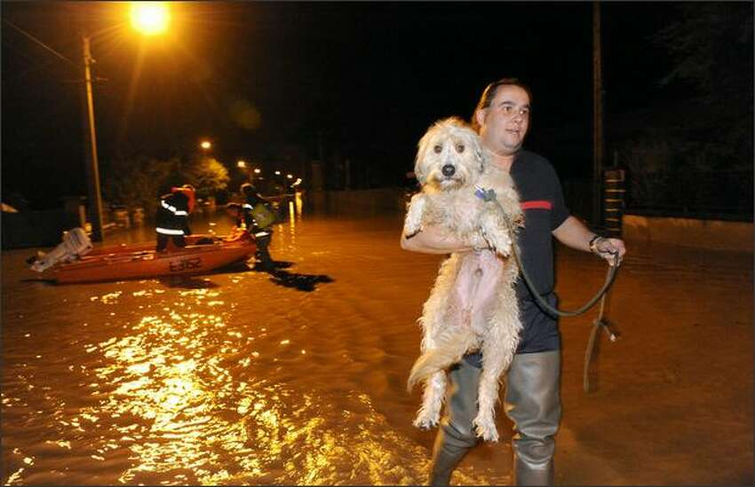 A fireman holds a dog during the evacuation of inhabitants in a flooded area of Brassac-les-Mines, central France, after the Allier river bursted its banks following torrential rains.