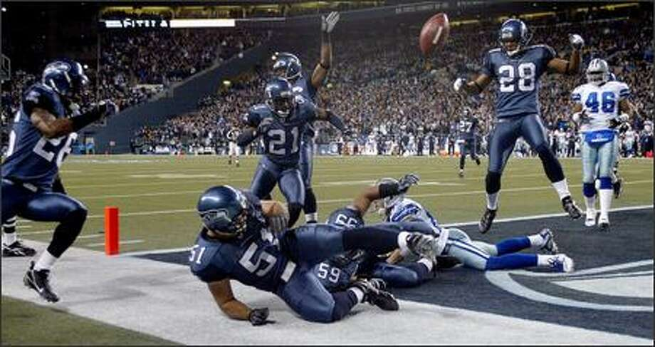 Seahawks linebacker Lofa Tatupu (51) bats a Dallas fumble back into the end zone where it was recovered by safety Michael Boulware (28) in the fourth quarter. The play was ruled a safety and cut Dallas' lead to 20-15. Photo: Mike Urban, Seattle Post-Intelligencer / Seattle Post-Intelligencer