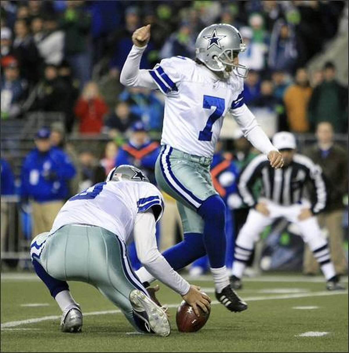 Dallas kicker Martin Gramatica steps over the ball as Tony Romo fumbles late in the fourth quarter.